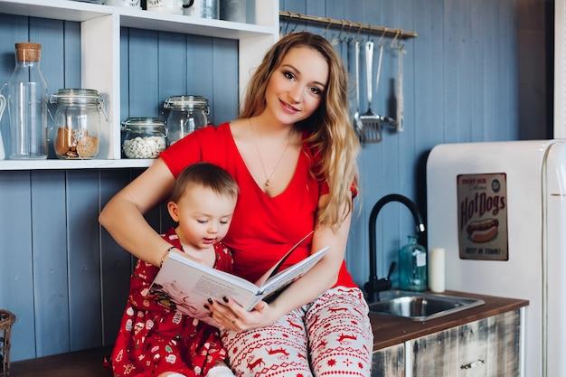 Schöne mutter mit kleiner tochter im weihnachtspyjama-lesebuch an der küche.