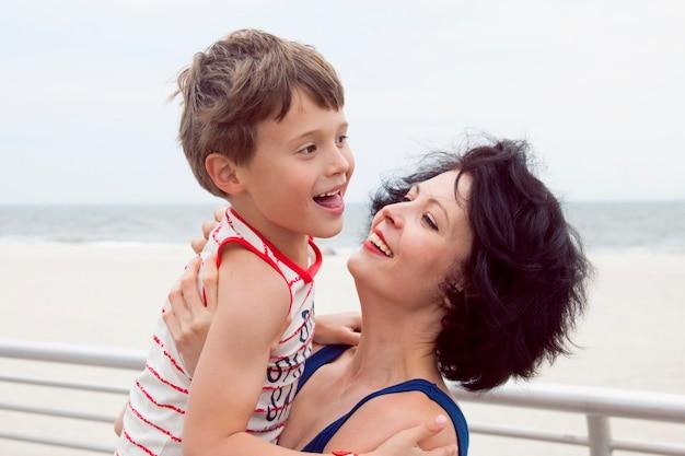 Schöne mutter mit süßem sohn beim spaziergang familienfoto am strand