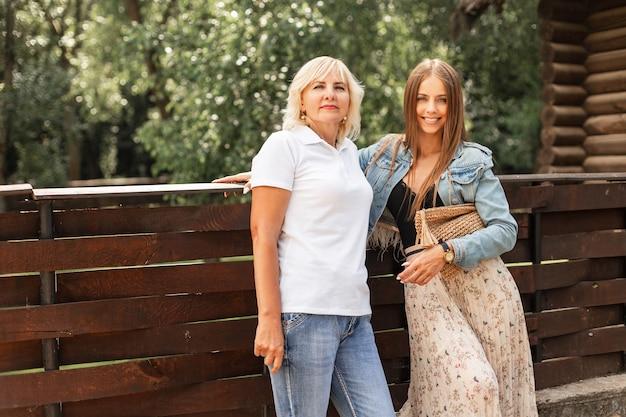Schöne mutter mit tochter in modischer jeanskleidung in weißem polo und vintage-kleid mit einer handtasche in der nähe einer holzwand in der natur