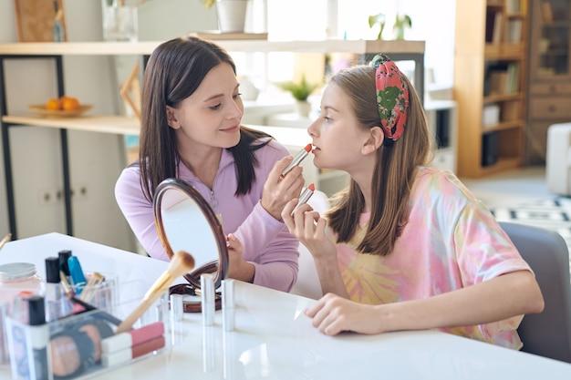 Schöne mutter mittleren alters, die lippenstift auf die lippen der töchter aufträgt, während sie lehrt, make-up zu tun
