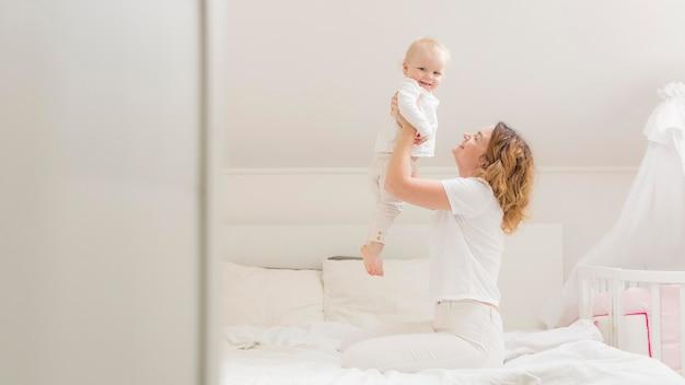 Schöne mutter spielt mit ihrem baby