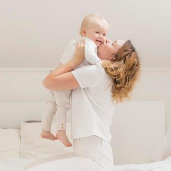 Schöne mutter spielt mit ihrem kind