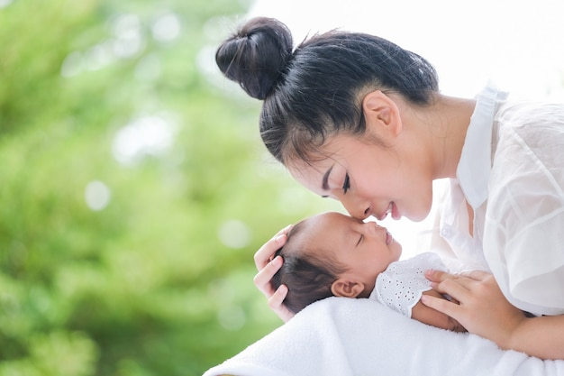Schöne mutter und baby in einem asiatischen park