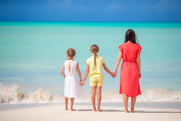 Schöne mutter und ihre entzückenden kleinen töchter am strand