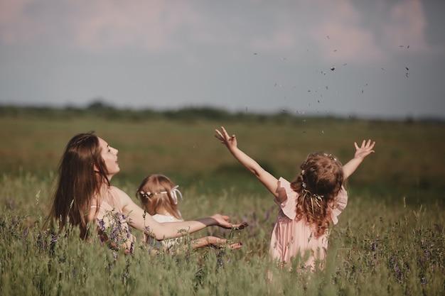 Schöne mutter und ihre kleine tochter im freien. natur. outdoor portrait der glücklichen familie. schönheits-mama und ihr kind, die zusammen im park spielen. alles gute zum muttertag joy. mama und baby