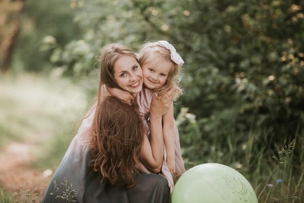 Schöne mutter und ihre kleine tochter im freien. natur. schönheits-mama und ihr kind, die zusammen im park spielen. outdoor portrait der glücklichen familie. alles gute zum muttertag joy. mama und baby