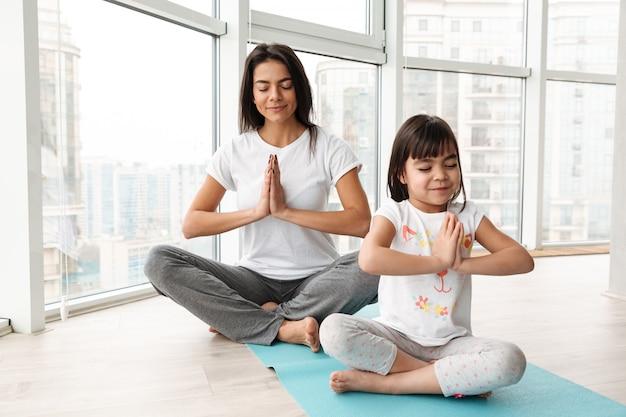 Schöne mutter und kind meditieren zu hause, sitzen beine gekreuzt auf matte und machen yoga-geste mit handflächen zusammen