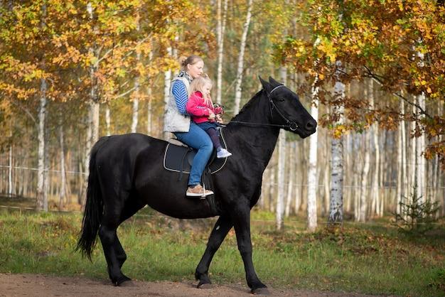 Schöne mutter und kleine mädchen tochter, die schwarzes pferd reitet, hat glückliche lustige gefühle
