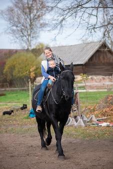 Schöne mutter und kleiner baby-sohn, der schwarzes pferd reitet, hat glückliche lustige gefühle