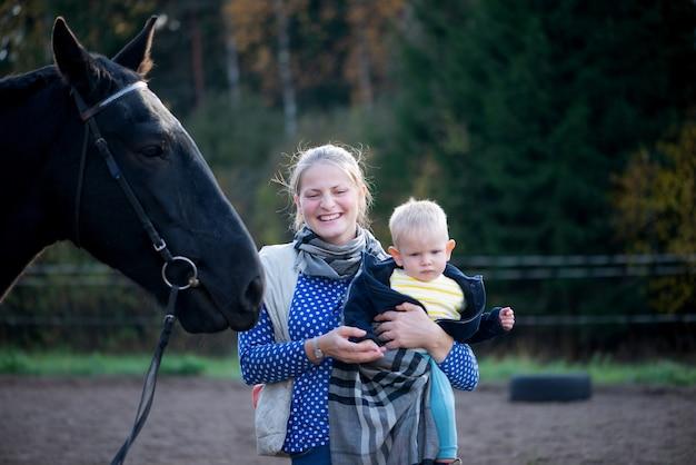 Schöne mutter und kleiner baby-sohn mit schwarzem pferd im freien