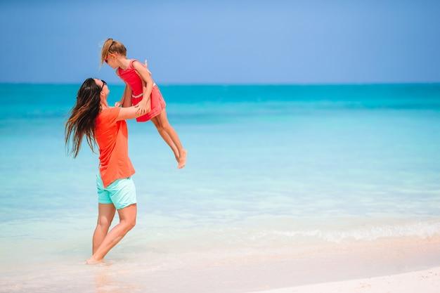 Schöne mutter und tochter am karibikstrand genießen sommerferien.