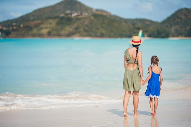 Schöne mutter und tochter am karibischen strand sommerferien genießend.
