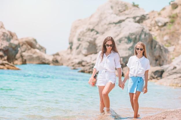 Schöne mutter und tochter am strand genießen sommerferien.
