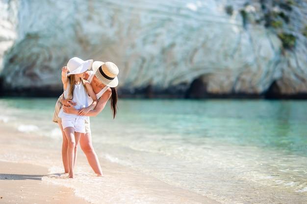 Schöne mutter und tochter am strand sommerferien genießend.