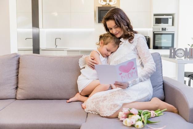 Schöne mutter und tochter, die auf sofa in der wohnzimmerlesegrußkarte sitzt