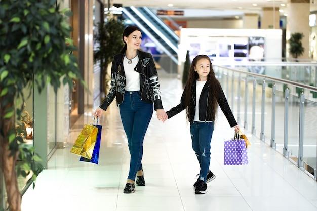 Schöne mutter und tochter lächeln beim einkaufen im einkaufszentrum