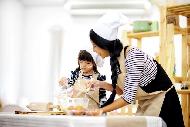 Schöne mutter unterrichtet ihre tochterhacke, um frühstück in der küche vorzubereiten