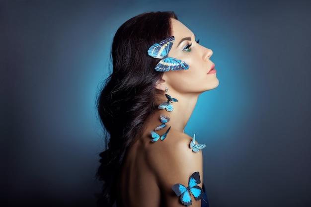 Schöne mysteriöse frau mit den schmetterlingen blau
