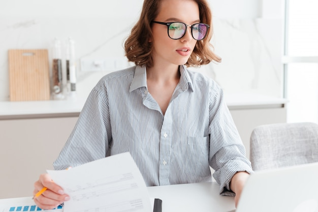 Schöne nachdenkliche frau in brille und gestreiftem hemd, die mit dokumenten zu hause arbeitet