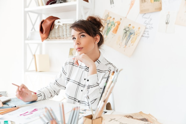 Schöne nachdenkliche frau modedesignerin, die an ihrem arbeitsplatz sitzt