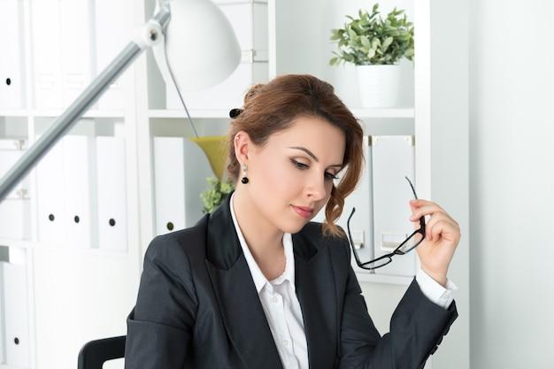 Schöne nachdenkliche geschäftsfrau, die an ihrem arbeitsplatz im büro sitzt und brille in ihrer hand hält.