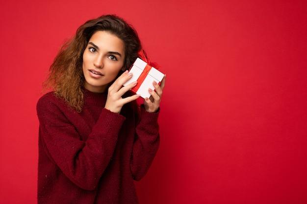 Schöne nachdenkliche junge brünette lockige weibliche person isoliert über rotem hintergrundwand tragen