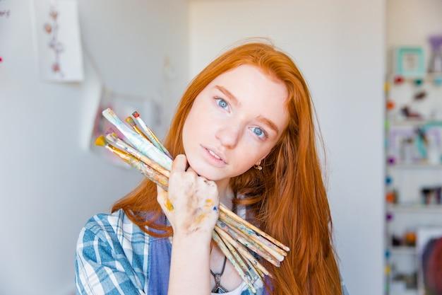Schöne nachdenkliche junge malerin mit langen roten haaren, die pinsel im kunststudio hält