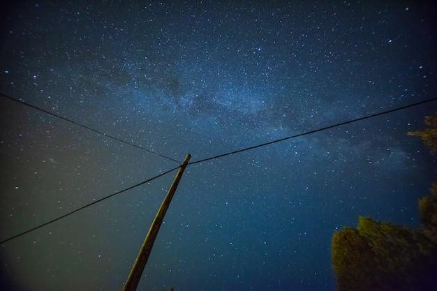 Schöne nachthimmellandschaft mit sternen und elektrischer post