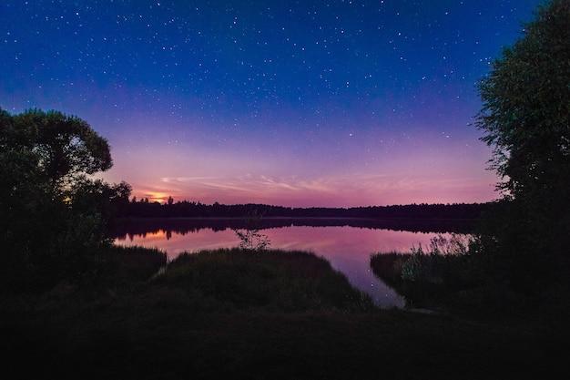 Schöne nachtlandschaft auf dem waldsee mit sternen und reflektierten wolken im wasser im frühjahr. bunter himmel. natur hintergrund