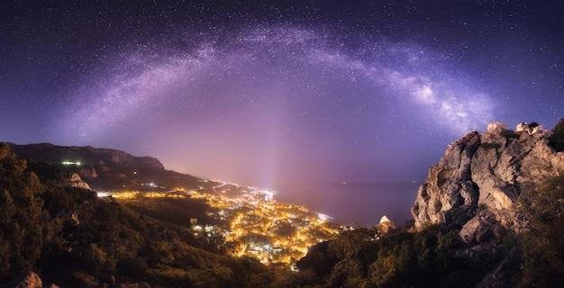Schöne nachtlandschaft mit milchstraße gegen stadtlichter