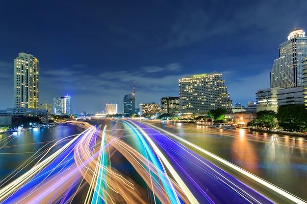 Schöne nachtstadt bangkok mit geschwindigkeitslicht auf fluss