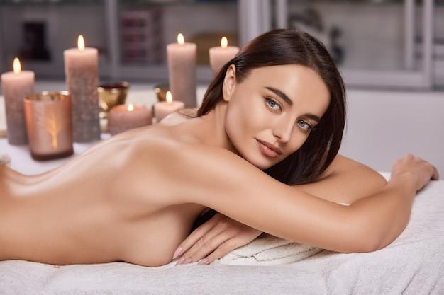 Schöne nackte frau, die im spa-salon liegt und mit vielen kerzen zur seite schaut
