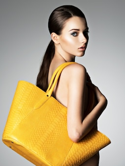 Schöne nackte frau hält modehandtasche, die im studio aufwirft
