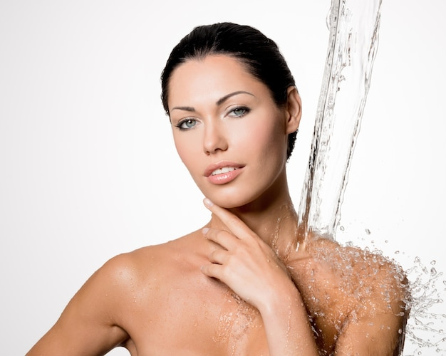 Schöne nackte frau mit nassem körper und spritzer wasser