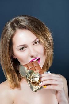 Schöne nackte junge blonde frau mit hellem make-up, das schokoriegel isst.