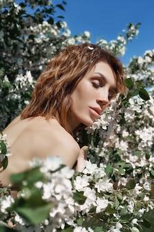 Schöne nackte kunstfrau in den niederlassungen und im laub eines blühenden apfelbaums in der natur. schöner schlanker körper, naturkosmetik und schönheit. apfelblüten auf mädchenkörper
