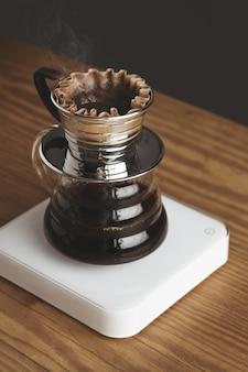 Schöne nahaufnahme der transparenten chrom-filterkaffeemaschine mit geröstetem gefiltertem kaffee, lokalisiert auf dickem holztisch im café-laden. weiße gewichte. dampf. brutal.