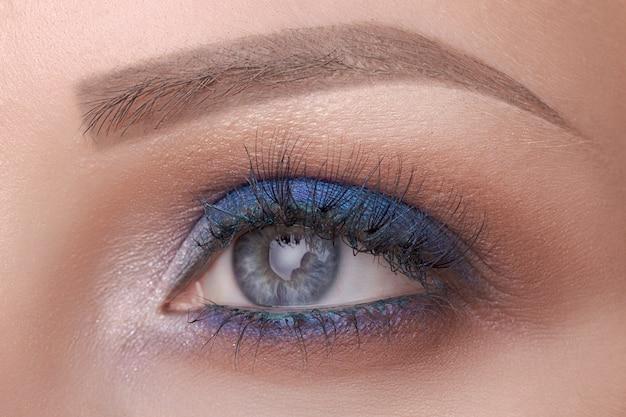 Schöne nahaufnahme des blauen auges, helles make-up