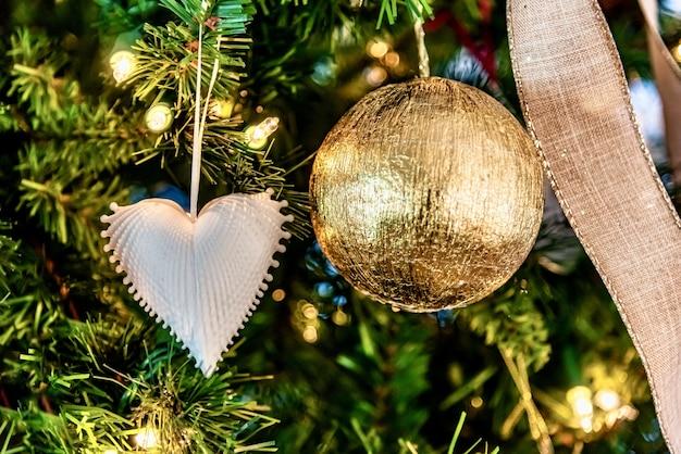 Schöne nahaufnahme einer weißen herzförmigen verzierung und einer goldenen kugel auf einem weihnachtsbaum