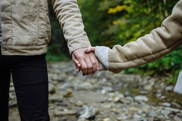 Schöne nahaufnahme von paarhänden, die sich gegenseitig halten schönes paar, das im berg wandert. liebeskonzept.