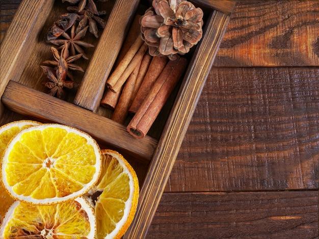 Schöne nahaufnahme von trockenen orangen, von zimtstangen und von stern anis, tannenzapfen in einer holzkiste