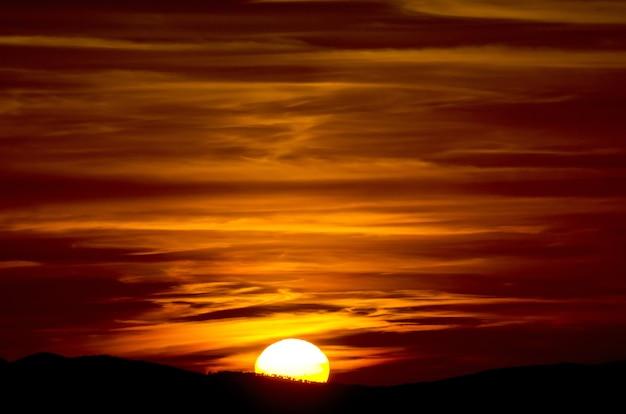 Schöne nahaufnahmeaufnahme eines sonnenuntergangs mit gelesenem himmel und halber sonne in der toskana, italien