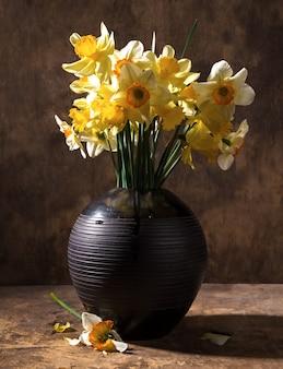 Schöne narzissen in schwarzer vase auf holzuntergrund auf holzuntergrund
