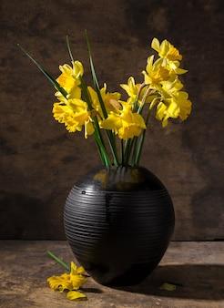 Schöne narzissen in schwarzer vase auf holzuntergrund