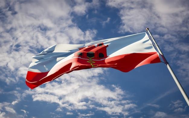 Schöne nationalstaatsflagge von gibraltar, die auf blauem himmel flattert