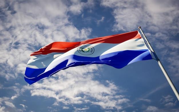Schöne nationalstaatsflagge von paraguay, die auf blauem himmel flattert