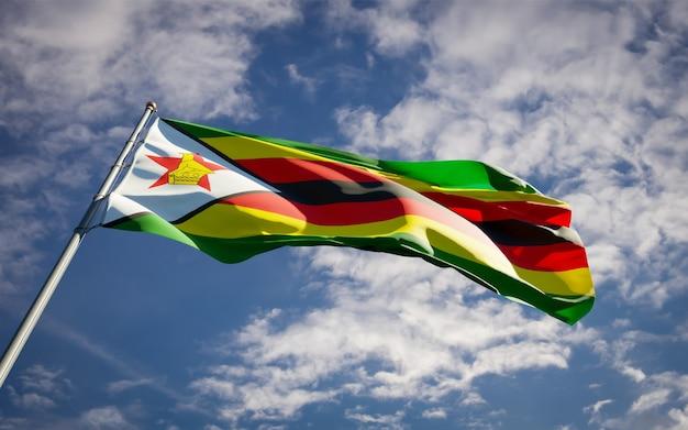 Schöne nationalstaatsflagge von simbabwe, die auf blauem himmel flattert