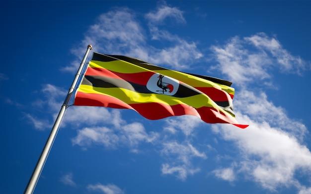 Schöne nationalstaatsflagge von uganda, die auf blauem himmel flattert
