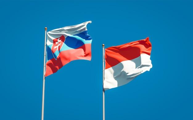 Schöne nationalstaatsflaggen der slowakei und indonesiens zusammen auf blauem himmel