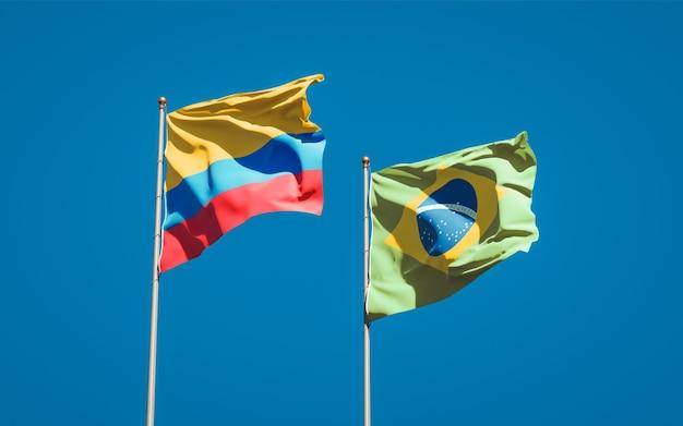 Schöne nationalstaatsflaggen von brasilien und von kolumbien zusammen auf blauem himmel